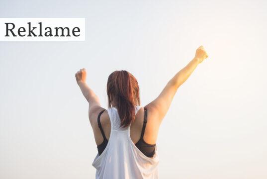 Kvinde i træningstøj med armene rejst